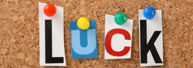 L U C K letters pinned to a cork board