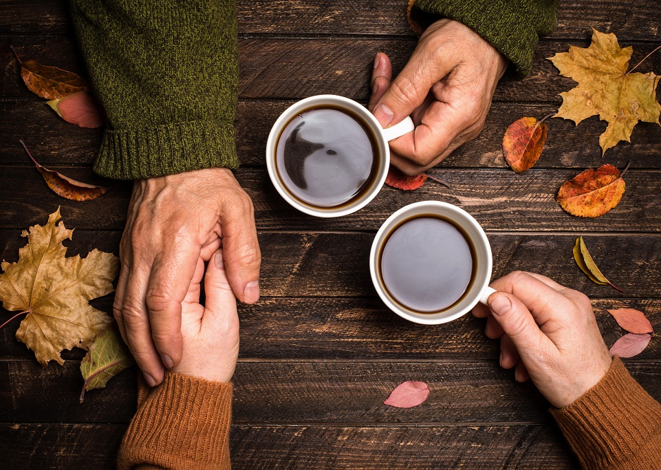 Old people holding hands on rustic table covered with autumn leaves